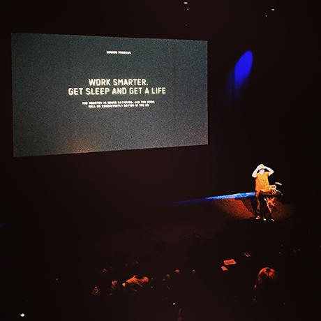 Danny Yount ser ut over publikum, gir sitt visdomsord og spør om dem som jobber mer enn 10 timer om dagen kan rekke opp hånda